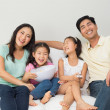 Happy family of four watching tv in living room — Stock Photo