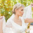 Content blonde bride holding her veil out — Stock Photo