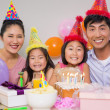Stock Photo: Family of four with cake and gifts at a birthday party