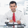 Smiling young businessman writing in diary at office — Stock Photo #37834465