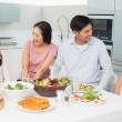 Cheerful family of four enjoying healthy meal in kitchen — Stock Photo