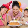 Stock Photo: Girls looking at mother with cake at birthday party