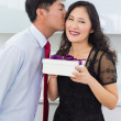 Young man kissing a woman as he gives her a gift box — Stock Photo