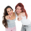 Happy young friends pointing against white background — Stock Photo