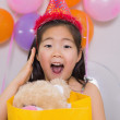 Shocked little girl with gift at her birthday party — Stock Photo