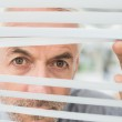 Close-up of a mature businessman peeking through blinds — Stock Photo #37836391