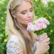 Blonde bride smelling her bouquet — Stock Photo