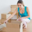 Woman unwrapping boxes in new house — Stock Photo #37836753