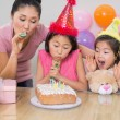 Stock Photo: Girls and mother blowing noisemakers at birthday party