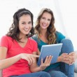 Female friends using digital tablet in the living room — Stock Photo