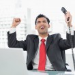 Businessman cheering with telephone receiver at office — Stock Photo