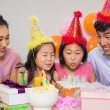 Stock Photo: Family with cake and gifts at a birthday party