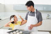 Cheerful girl with her father preparing cookies in kitchen — Stock Photo