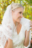 Beautiful blonde bride holding her veil and smiling — Stock Photo