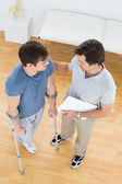 Male therapist and disabled patient with reports — Stock Photo