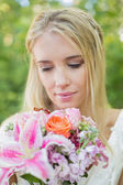 Blonde smiling bride holding bouquet — Stock fotografie
