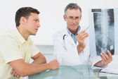 Médecin expliquant la radiographie des poumons au patient en fonction — Photo