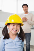 Cute girl in yellow hard hat with father in background — Stock Photo