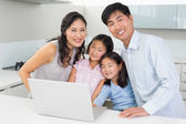 Portrait of a happy family of four with laptop in kitchen — Stock Photo