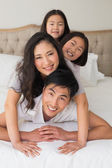 Cheerful family of four lying over each other in bed — Stock Photo