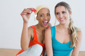 Two cheerful female friends with house keys — Stock Photo