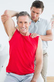 Physiotherapist stretching a smiling mature mans arm — Stock Photo