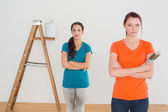 Friends with paint brushes and ladder in a new house — Stock Photo
