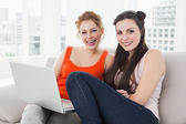Female friends using laptop together at home — Stock Photo