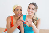 Portrait of two cheerful female friends with house keys — Stock Photo