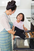 Girl helping her mother prepare cookies in kitchen — Stock Photo