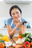 Smiling woman text messaging in front of vegetables in kitchen — Stock Photo