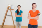 Friends with paint brushes and ladder in a new house — Foto Stock
