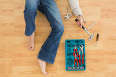 Man lying with several tools on parquet floor — Stock Photo