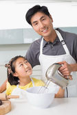 Man with his daughter using electric whisk into bowl in kitchen — Stock Photo