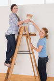 Friends with paintbrush and can on ladder in a new house — Stock Photo