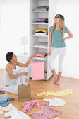 Happy young women arranging clothes in shelf — Foto Stock