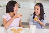 Girls enjoying cookies and milk in kitchen — Stockfoto