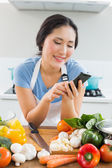 Woman text messaging in front of vegetables in kitchen — Stock Photo