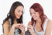 Smiling pretty young woman painting friend's nails — Stock Photo