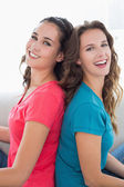 Female friends sitting back to back in living room — Stock Photo
