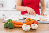 Mid section of a woman with recipe book and vegetables — Stock Photo