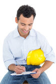 Handyman with yellow hard hat writing in clipboard — Stock Photo