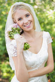 Pretty smiling bride holding her bouquet wearing a veil — Stock Photo