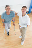 Terapeut och funktionshindrade patient med rapporter på gym sjukhus — Stockfoto