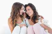 Female friends sitting on bed with arm around — Stock Photo