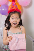 Shocked girl opening gift box at her birthday party — Stock Photo