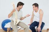 Przyjazny fizjoterapeuty tłumacząc kręgosłupa pacjenta — Zdjęcie stockowe