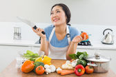 Thoughtful woman chopping vegetables in kitchen — Stock Photo
