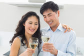Loving young couple with wine glasses in kitchen — Stock Photo