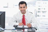 Smiling young businessman writing in diary at office — Stock Photo